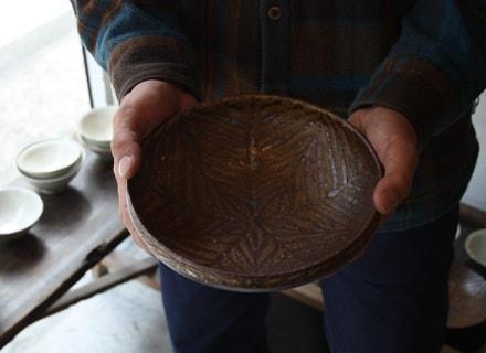 鉄絵のシリーズのお皿を手に持っているところ
